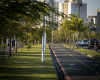 Park in the city with cars and people passing by. royalty free stock images