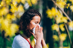 In the park. Cute girl in the park, sneezing, having spring allergies Royalty Free Stock Photos