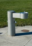 Park Drinking Fountain. Drinking fountain in park installed in a sidewalk on the edge of the grass stock photos