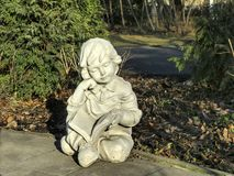 Garden figurine. Child with a book stock photography