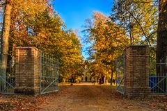 Park entrance to a castle in autumn with trees royalty free stock photos