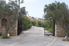 Park entry with open wrought-iron gate in gradient back and shut off the track. On a summer day Royalty Free Stock Photos