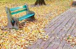 Park in the fall. Image of a park bench surrounded by fallen leaves Stock Photos