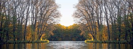 Park in the fall in the sun. Reflection in water and mirror symmetry. Rays of sunset on the autumn foliage. Charming autumn. October Royalty Free Stock Image
