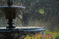 Park fountain splashes. Photo of a tiered park fountain cascading splashes with spring flowers in background ideal for own text etc Stock Photos