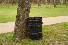 Park garbage can by tree with trees and grass Royalty Free Stock Image