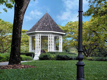 Park garden pavilion. This is taken in the singapore botanic gardens, it is a very lovely little spot. There is a couple in the pavilion in this shot Royalty Free Stock Image