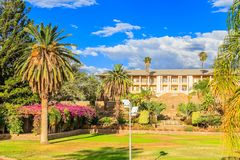 Park and garden with yellow palace building hidden behind tall palms, Windhoek, Namibia. Africa african architecture assembly blue capital center central city stock photos