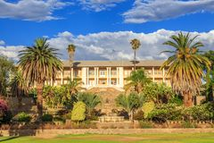 Park and garden with yellow palace building hidden behind tall palms, Windhoek, Namibia. Africa african architecture assembly blue capital center central city royalty free stock photo