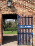 Park gate. An open blue gate with a sign saying gate to the park stands by an arched entrance in a brick wall topped by a old-fashioned carriage light Stock Photography