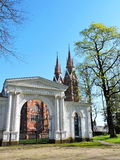 Park gate and red church, Lithuania. White park gate and St. Jacob Catholic Churc In Sveksna, Lithuania stock photos