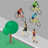 Park girl and guy are jogging, cyclist rides along road Stock Photos