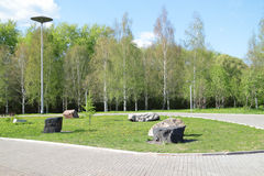 Park with green grass, large decorative boulders Stock Images