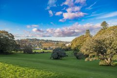 Park with green grass and trees lit by the evening sun. Under a blue cloudy sky in Monte Cecilia park in Hillsborough Auckland Royalty Free Stock Photography