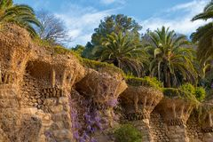 Park Guell in Barcelona, curved stone walls. Curved stone walls with blooming plants, at park Guell in Barcelona, Catalonia, Spain, architectural details Stock Photography
