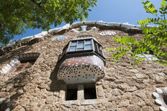 Park Guell, Barcelona. Stone wall and mosaic balcony with fresh summer acacia branches at the entrance to famous Parc Guell in Barcelona stock photography
