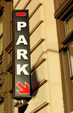 Park Here. A parking sign in white letters with red directional arrow Royalty Free Stock Photo