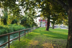 Park and houses. A small and peaceful park with a river passing by and some houses on the background Stock Photo