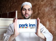 Park Inn by Radisson hotel logo. Logo of Park Inn by Radisson hotel on samsung tablet holded by arab muslim man. Park Inn is a fresh and energetic mid-market stock images