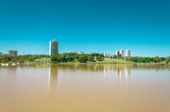 Park lake with vegetation, trees and some buildings in the background Royalty Free Stock Images