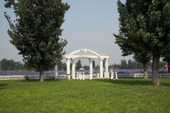 Park landscape architecture, white arch gate, fence Stock Photo