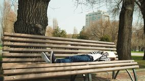 Park leisure time. Young cute tired teen lying and relax on bench with book. outdoor education royalty free stock image