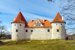 Park with medieval castle with orange roof in Bauska town, Latvia Stock Photos