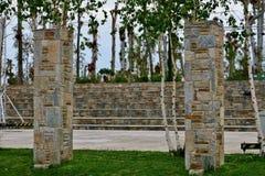 Park met lange bomen met stappen en kolommen van stenen royalty-vrije stock foto's