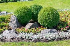Park mit Büschen und Steinen Stockbild
