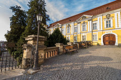 Park near ancient monastery. Park with lantern and benches near ancient yellow monastery Stock Image