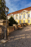 Park near ancient monastery. Park with lantern and benches near ancient yellow monastery Royalty Free Stock Photography