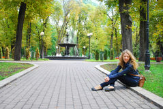 In the park near the fountain, girl sits on the curb. Royalty Free Stock Images