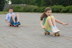 In the Park, outdoors, a boy and a girl riding a skateboard, sitting on it, on the stone blocks royalty free stock photography
