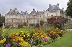 Park in paris jardin luxembourg. Park with flowers lawn and alley in paris france jardin luxembourg palace building in background summer day overcast horizontal Stock Photos