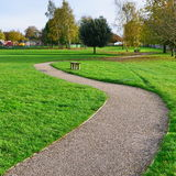 Park Pathway. Scenic View of a Winding Stone Pathway in a Lush Green Park Royalty Free Stock Images