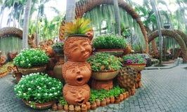 Park Pattaya Nong Nooch mit einem ungewöhnlichen Landschaftsentwurf von keramischen Töpfen in Form von lustigen Gesichtern und vo lizenzfreies stockbild