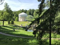 Park Pavilion-Rotunda `Temple of Friendship`, stylized as antiquity, in Pavlovsk Park on a summer sunny day. People walk in the park, relax and paint. Top view stock photos