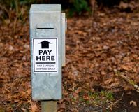 Park pay station drop box with grass and brown leaves royalty free stock photos