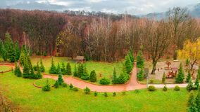 Park with playground in autumn. Gloomy rainy weather in mountains. green lawn and leafless forest in november royalty free stock photography