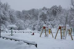 Park playground covered with fresh white snow after blizzard in winter. Trees Royalty Free Stock Images
