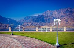 Park with a pleasing view. Traditional white lampposts in a park with a beautiful mountain scenery as backdrop. From Muscat, Oman stock photo