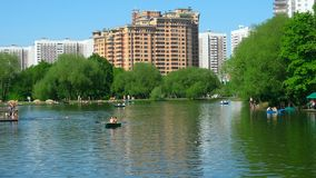 Park pond. Pond in  a park in Moscow at summer weekend with boats, people, trees, ducks and surrounding buildings Stock Photography