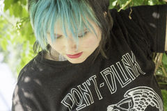 In the Park. Punk girl with blue hair looks down in deep thought while at the park Stock Photography