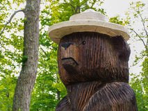Park Ranger Bear - Life Size Wood Carved Statue. Full size brown bear standing - (head and shoulders view) wearing a tan park ranger style hat (looks a bit like Royalty Free Stock Photo