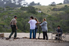 Park ranger. Carmel by the sea, California - May 06 : Park ranger checking on a group of students filming on the beach, May 06 2015 Carmel by the sea, California royalty free stock photography