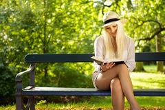 Park recreation. Cute woman sitting on a bench in a park reading a book. Copyspace left Royalty Free Stock Photo