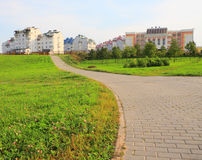 Park at residential area. Pathway in park in residential area leading to buildings Stock Photo