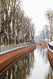 Park with river and embankment covered with snow Stock Photos
