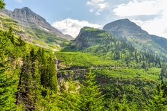 The Park Road Cuts Along the Mountain Side in Glacier National Park royalty free stock images