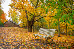 Park scenery in october. Lonely bench and fallen leaves in park in october Royalty Free Stock Photos